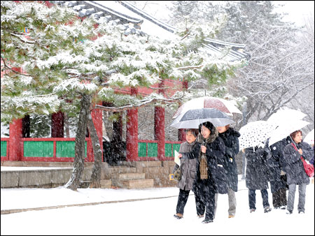 Asian tourists enjoy the snow-covered scenery of...