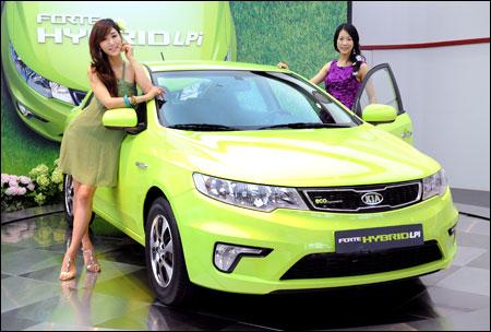 Models pose with kia motors hybrid sedan forte hybrid for Kia motors latest models