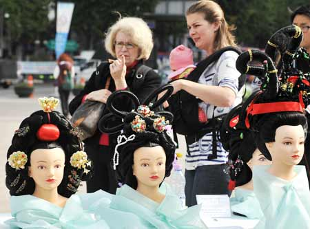 Foreign Visitors Look At Mannequins With