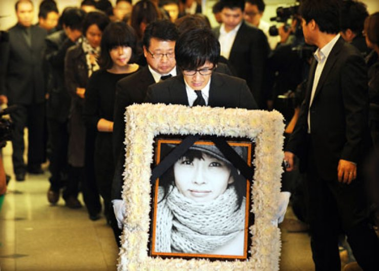 Singer Choi Jin-young carries the photo of Choi Jin-sil, his late elder sister and the country's iconic actress, during a funeral ceremony at a Seoul hospital in October 2008 after she killed herself. He also took his own life in 2010. /  Korea Times file