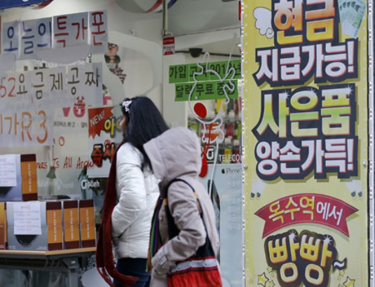 Pedestrians pass by a local handset outlet in downtown Seoul. Amid soaring demand for Long-Term Evolution (LTE) enabled portable devices, the nation's three carriers - KT, SK Telecom and LG Uplus - will bid in an upcoming auction of a license for the 1.8 GHz frequency spectrum to gain a competitive edge in their LTE services.                                     / Korea Times file
