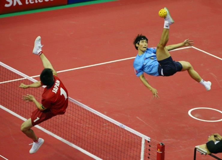 South Korean sepak takraw player Im An-soo, right, kicks the ball during a preliminary match against Japan held at the Bucheon Gymnasium, Saturday./ Yonhap