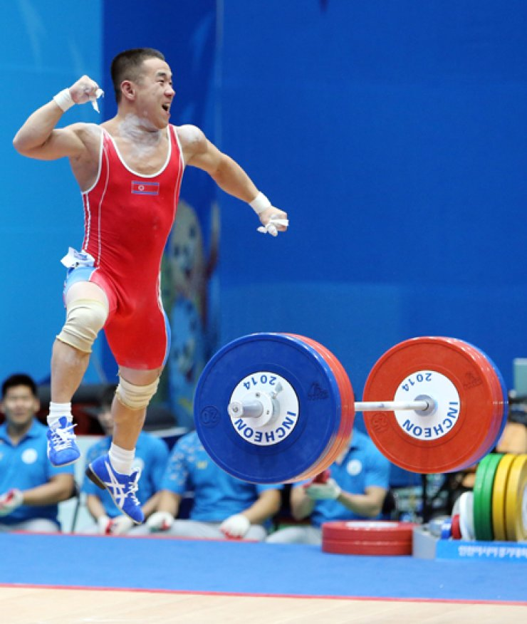North Korean weightlifter Um Yun-chol jumps out of excitement after winning the gold medal with a new world record of 298 kilograms duringthe men's weightlifting 56-kilogram-class event at the Moonlight Festival Garden Weightlifting Venue, Saturday./ Yonhap