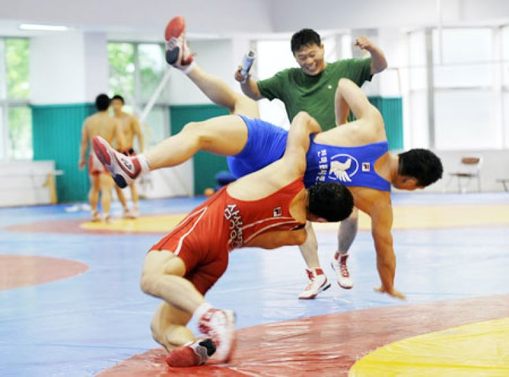 National wrestling team coach An Han-bong trains with atheletes ahead of the 2012 London Olympic Games.                                                / Korea Times file