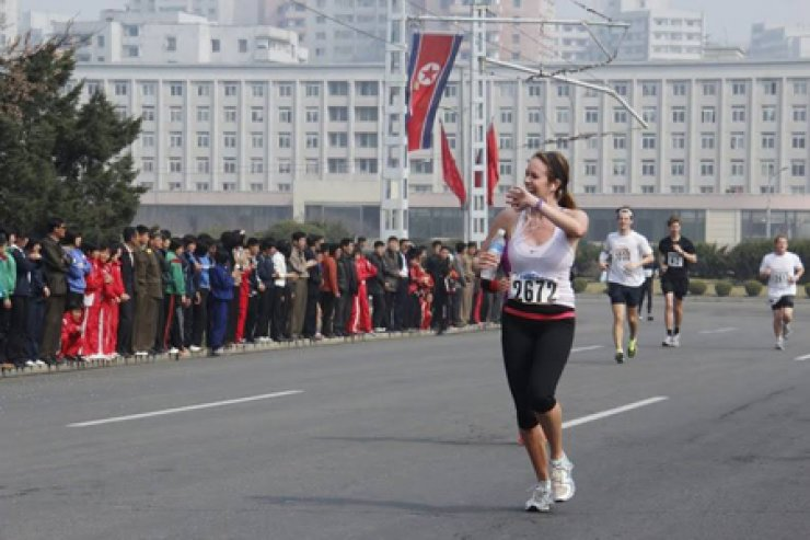 A runner waves her hand to North Korean locals during the 2014 Pyongyang Marathon, which opened to foreign amateurs for the first time in this April. / Courtesy of Young Pioneer Tours