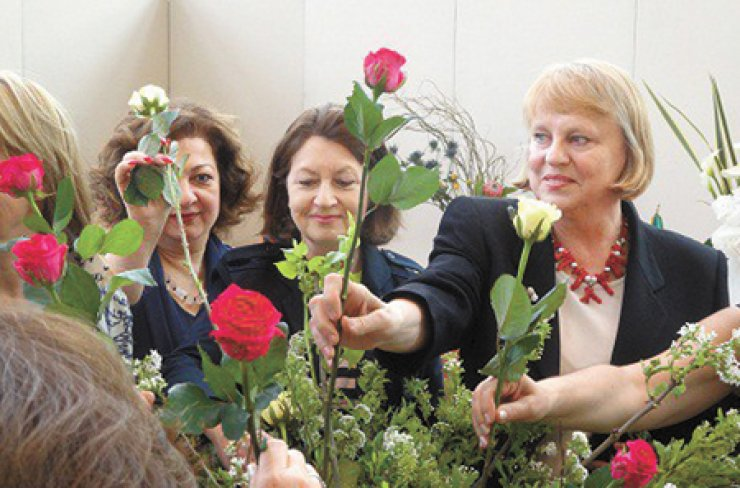Spouses of ambassadors put roses into a vase during the Seoul Garden Club Flower Show at the Raemian Gallery in Seoul on May 6. From left are Avazeh Kasrai from Iraq, Helen Paterson from Australia and Zofia Majka from Poland. / Courtesy of Australian Embassy