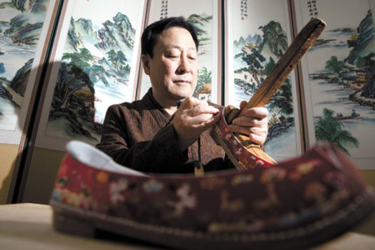 Hwang Hae-bong demonstrates how to make traditional shoes in his house inMacheon-dong, Seoul. / Korea Times photos by Choi Won-suk