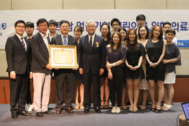 Prof. Baek Rong-min, fourth from left in the front row, a plastic surgeon at Seoul National University Bundang Hospital, smiles with his team of doctors and nurses after receiving an honor from the Vietnamese government at Melia Hanoi Hotel in Hanoi, June 17, for his decades of providing treatment for Vietnamese children with birth defects. / Courtesy of Seoul National University Bundang Hospital
