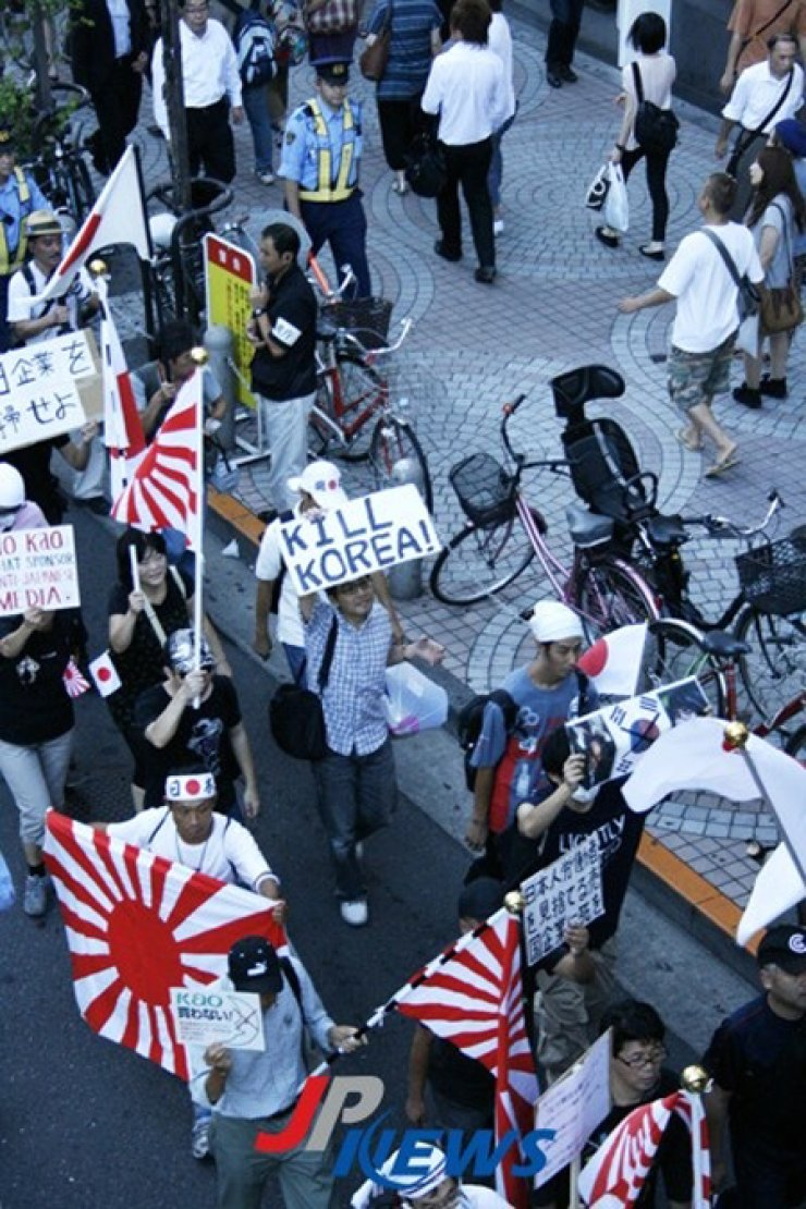 Anti-hallyu protesters march through the Shin-Okubo district in Tokyo, waving Japanese flags and holding signs with offensive messages against Korea in the left photo taken on May 19, 2013.  / Korea Times files
