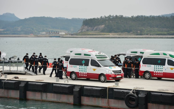 The bodies of passengers aboard the sunken Sewol ferry are transported to ambulances at Paengmok Port in Jindo, Tuesday. The death toll in the ferry disaster rose to more than 100 on the day. / Yonhap