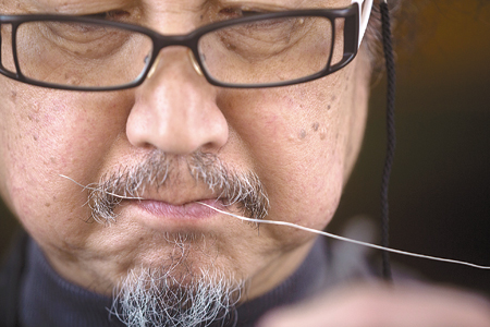 Kwack Hong-chan, a third-generation traditional metal artisan, shows the process of creating a traditional metal work in his workshop in Bucheon, Gyeonggi Province. Kwack carves on the surface of silver artifacts or other metal ornaments using a fine chisel, or inlays gold, silver or blackened copper threads in the grooves to make various patterns. / Korea Times photos by Shim Hyun-chul