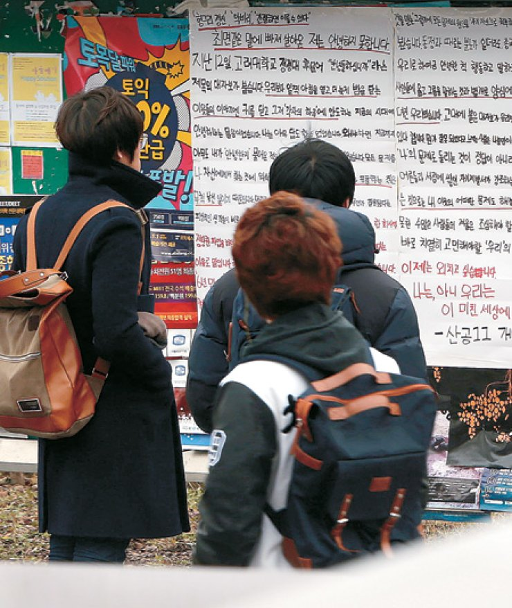 Students read a poster, titled 'I'm not doing well,' at a bulletin board at Korea Advanced Institute of Science and Technology in Daejeon, Monday. The poster is part of collegians' poster activism in support of a Korea University student's poster calling on students to pay greater attention to social issues. / Yonhap