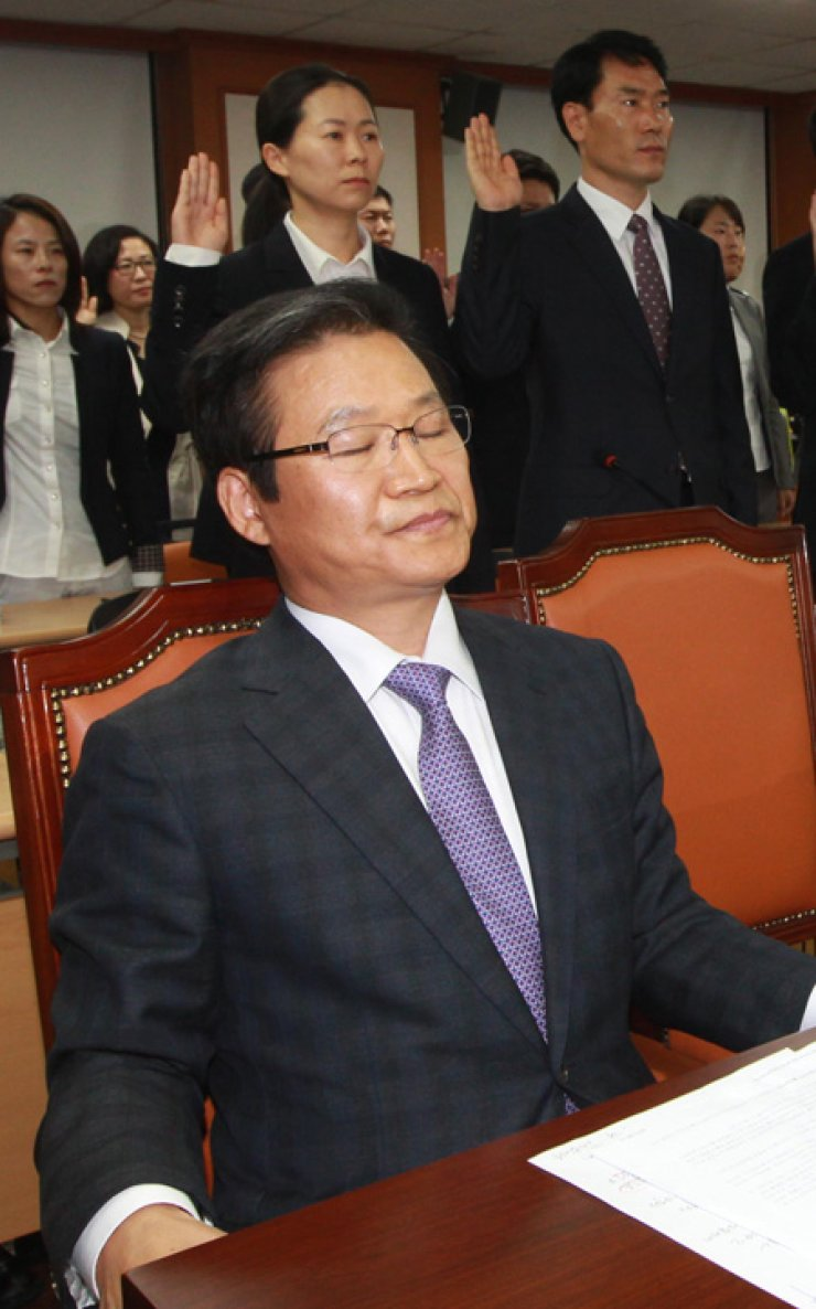 Kim Yong-pan, former chief of Seoul Metropolitan Police Agency (SMPA), sits before an audit by the National Assembly Security and Public Administration Committee, Tuesday, refusing to take the oath, while other participants stand up to do so. Kim appeared before the session to face questions about the SMPA's downscaled investigation into the National Intelligence Service's alleged meddling in the 2012 presidential election. He stated his ongoing trial as a reason not to take the oath. / Yonhap