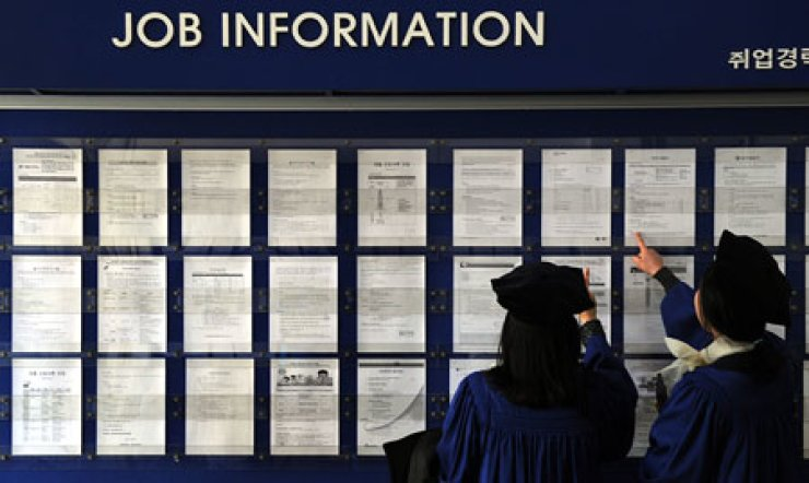 Two university graduates look at recruitment information on a bulletin board on campus. It has become increasingly hard for graduates to land decent jobs as companies hire fewer recruits amid the sluggish economy.                                                                                                                   / Korea Times file