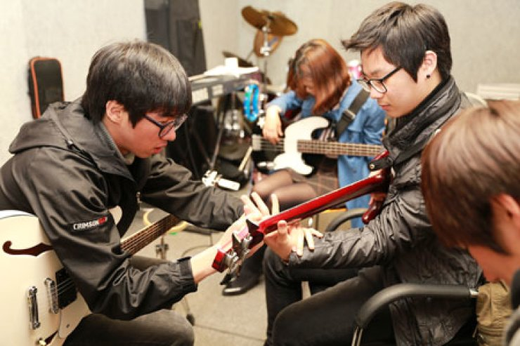 A senior club member teaches juniors how to play the guitar in the rock band club room at the Hankuk University of Foreign Studies in Seoul on Monday. The club runs programs to strengthen bonds between seniors and juniors.                                                         / Korea Times photo by Yoon Sung-won