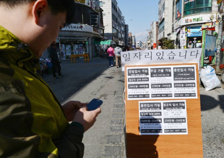 A foreign resident is looking at a street bulletin board with employment information in Wongok-dong, Ansan, an industrial town south of Seoul.                                                                      / Korea Times photo by Shim Hyun-chul