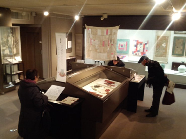 Japanese visitors look at Korean 'bojagi' or wrapping cloth and 'jumeoni' or pockets at the Koryo Museum of Art in Kyoto, Japan. The exhibition showcases some 40 pieces of bojagi and 25 of jumeoni through March 30 at the Koryo Museum of Art in collaboration with the Museum of Korean Embroidery in Seoul. /  Courtesy of Museum of Korean Embroidery