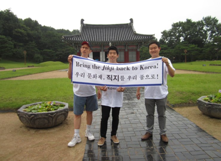 Richard Pennington, left, together with his colleagues in the Committee to Bring 'Jikji' Back to Korea, an NGO he formed last year, poses for a photo holding the committee's symbol banner at Heungdeok Temple in Cheongju on Sept. 12. / Courtesy of Pennington