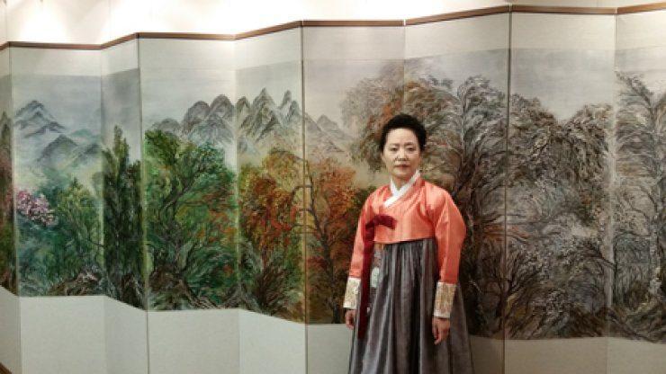 Thread artist Son In-sook poses with the folding screen titled 'A Dialogue With Life' at the Gaepodong Exhibition Center for Yewon Silgrim Art and Culture Foundation in southern Seoul. / Courtesy of Yewon Silgrim Art and Culture Foundation