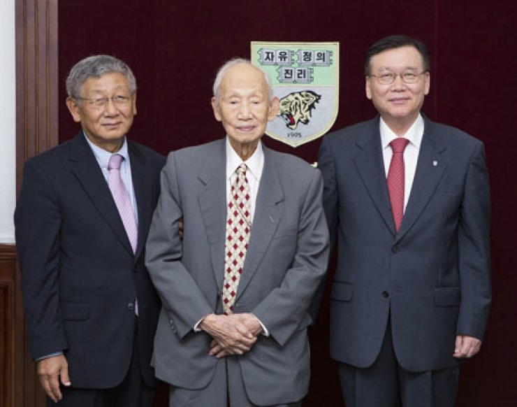 Woo Hyung-kyu, center, poses with Woo Jong-chun, emeritus professor ofSeoul National University, left, and Kim Byoung-chul, the president of KoreaUniversity, at the school president's office in Seoul, Thursday. Woo Hyung-kyu is the husband of Choi Duck-kyung, the emeritus professor of KoreaUniversity, who donated 1 billion won to the university for promotion of medical education. Prof. Choi's husband and her son Prof. Woo delivered thescholarship on behalf of Prof. Choi. / Courtesy of Korea University