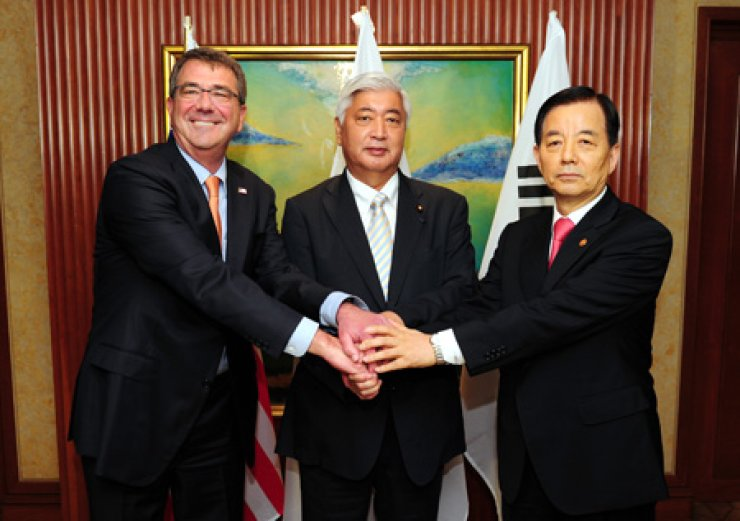 Defense Minister Han Min-koo, right, joins hands with U.S. Secretary of Defense Ashton Carter, left, and Japanese Defense Minister Gen Nakatani, before their talks on the sidelines of the 14th Asia Security Summit hosted by the International Institute for Strategic Studies in Singapore on May 30. The Korea Institute for Defense Analysis said in its January report that the U.S. deployment of the Terminal High Altitude Area Defense on the Korean Peninsula could accelerate a security alliance in two groups - Seoul, Washington and Tokyo in one and Pyongyang, Beijing and Moscow in the other. / Yonhap