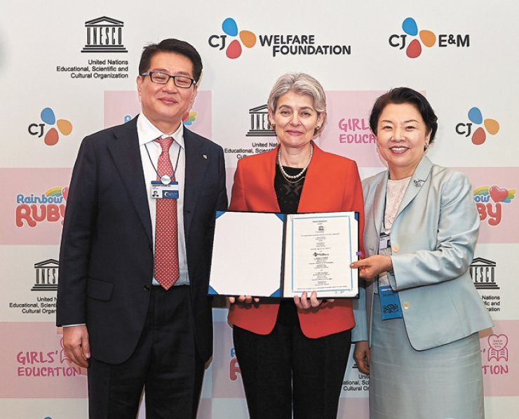 UNESCO Director-General Irina Bokova, center, stands with CJ E&M Executive Vice President Lee Sang-gill, left, and CJ Welfare Foundation Executive Vice President Min Hee-kyung after signing a partnershipagreement to promote the 'Better Life for Girls' global education campaign using the company's animation series 'Rainbow Ruby,' during the 2016 Global Education and Skills Forum in Dubai, the United Arab Emirates, Saturday. / Courtesy of the Global Education and Skills Forum