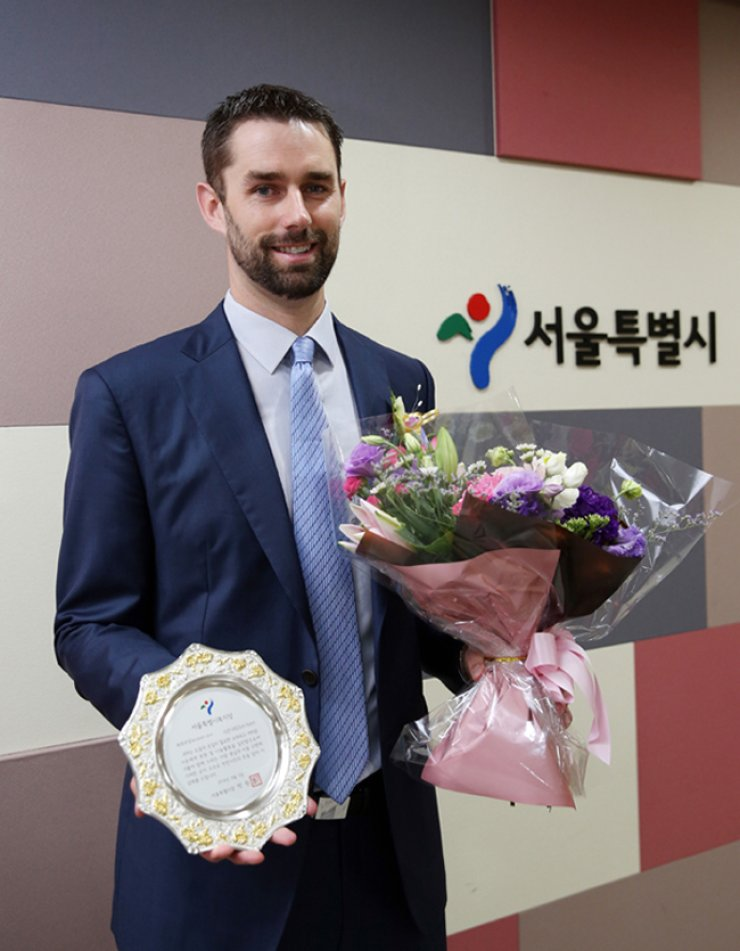 Dustin Nippert of the Doosan Bears poses with the award he received from the Seoul Metropolitan Governmentat City Hall, honoring his welfare work, Monday. / Courtesy of Doosan Bears