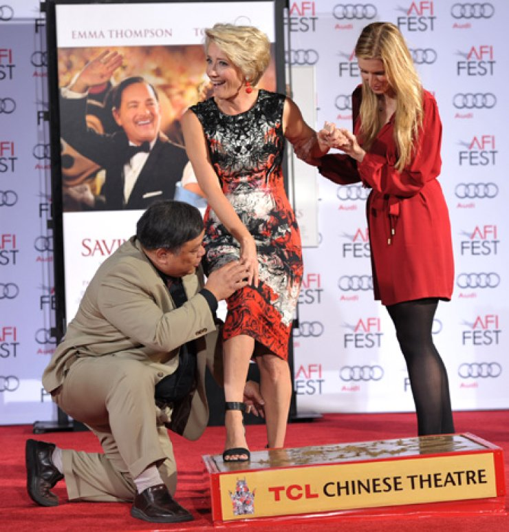 Emma Thompson, center, is honored with a hand and footprint ceremony at the TCL Chinese Theatre in Los Angeles on Thursday. Thompsonco-stars with Tom Hanks in the upcoming film 'Saving Mr. Banks.' / AP-Yonhap