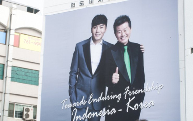 Singer Eru, left, and his father in this photo grace the wall of the Indonesian Embassy in Seoul.