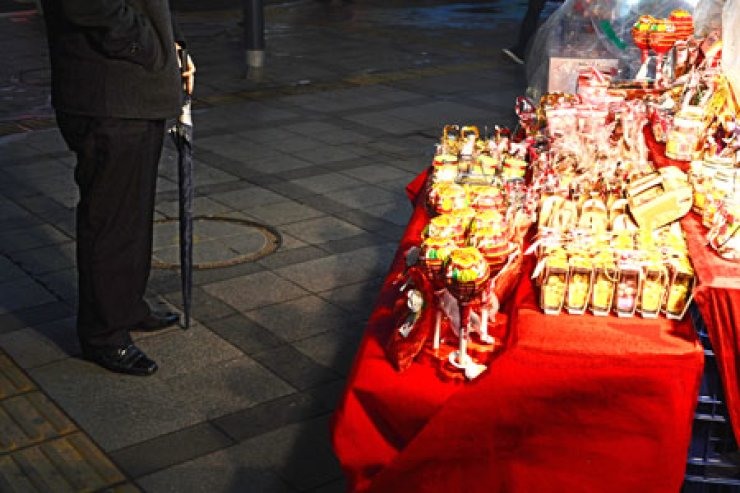 A man looks at gift-wrapped chocolate and candy products displayed in front of a convenience store in downtown Seoul, Wednesday. On 'White Day,' which falls on March 14, men are encouraged to give sweets or gifts to express affection to the women in their lives. In Korea, women give sweets to men on Valentine's Day. / Korea Times photos by Shim Hyun-chul