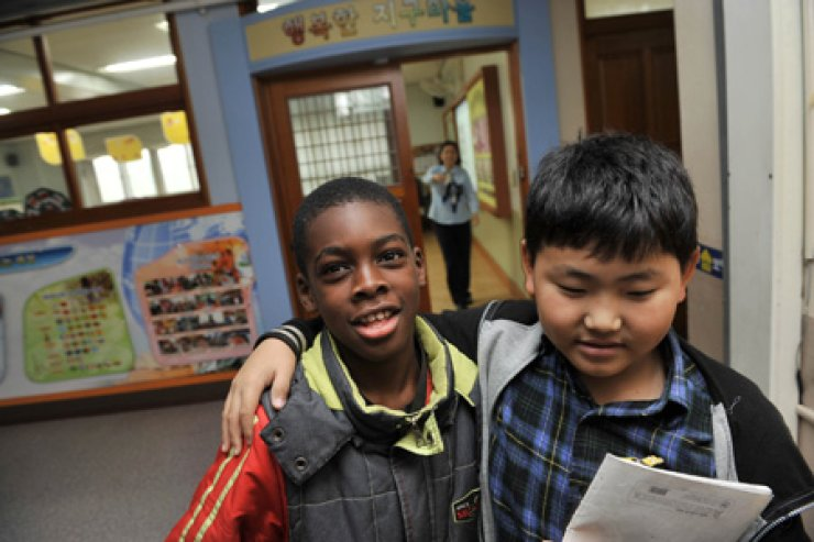 In the top photo, a student drapes his arm around his friend at Wonil Elementary School in Ansan, Gyeonggi Province, in this file photo taken on Oct. 26, 2011. / Korea Times files