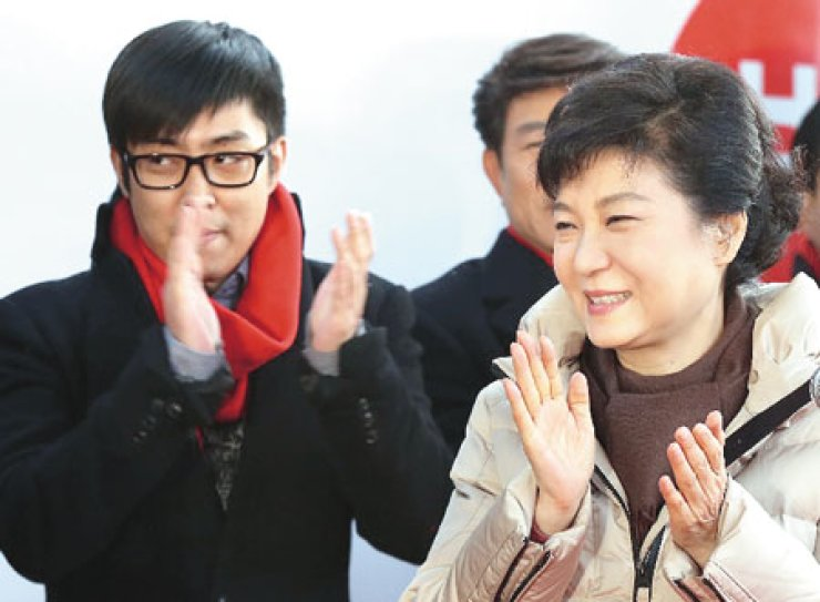 Singer Eun Ji-won, left, applauds along with President Park Geun-hye, his aunt, during a street campaign last December. / Korea Times file