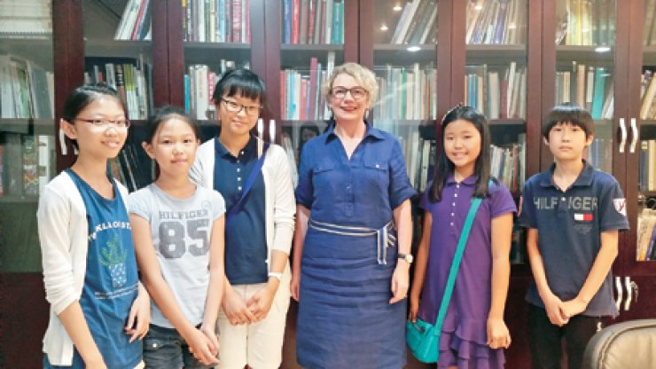 Irish Ambassador Aingeal O'Donoghue, fourth from left, and five elementary and middle school students pose for a photo at the Kevin O'Rourke Library of the Irish Embassy in Seoul, Aug. 8. / Korea Times