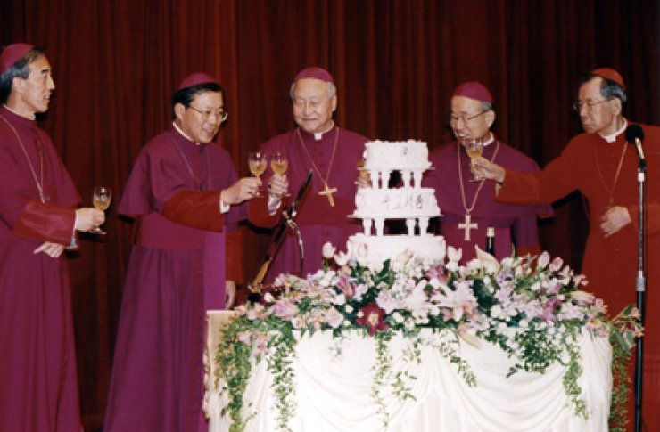 Andrew Yeom Soo-jung, second from left, toasts with the late Cardinal Stephen Kim Sou-hwan, right, and Cardinal Nicolas Cheong Jin-suk, center, after he was ordained as archbishop of Seoul in 2002. / Yonhap