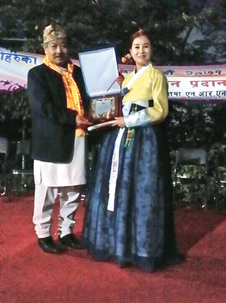Nepalese Ambassador Kaman Singh Lama, left, presents a certificate of appreciation to Min Ji-young, choreographer and Ari Art Companypresident, for her role in creating links between Korea and Nepal at the Wolgok soccer field in Seoul, on Oct. 5. / Korea Times