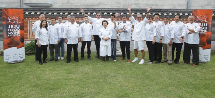 Eighteen chefs participating at the Jeju Food and Wine Festival cheer during a photo session. / Courtesy of Jeju Food and Wine Festival