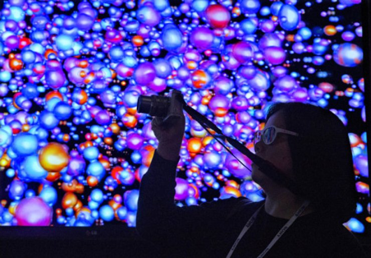 A visitor shoots video of an LG Ultra HD 3D wall display at the International Consumer Electronics Show in Las Vegas, Friday. / AP-Yonhap