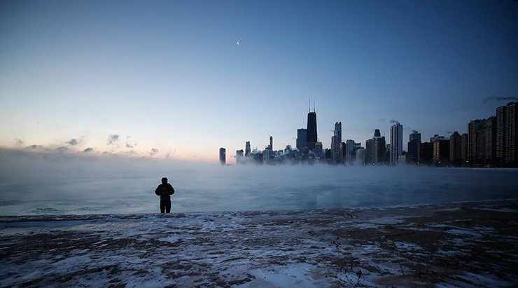 A man walks on North Avenue Beach as the sun rises over Lake Michigan in Chicago, Illinois, Jan. 20. The U.S. Midwest is experiencing a cold spell as a polar vortex sent temperatures plummeting below zero degrees Celsius. EPA