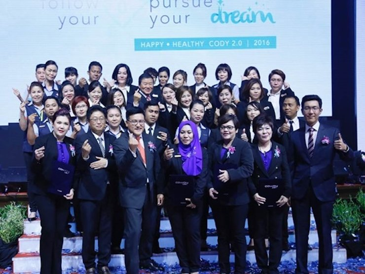 Coway Overseas Business Unit Director Paul Kim, third row fifth from left, and Coway Malaysia Managing Director Kyle Choi, front row third from left, pose with company staff during the firm's 10th anniversary event in Kuala Lumpur, Malaysia, last August. / Courtesy of Coway