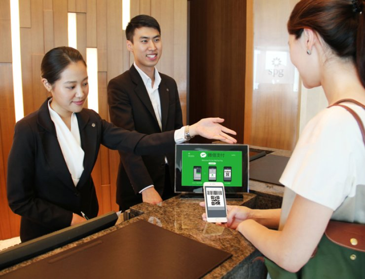 Sheraton Seoul D Cube City Hotel staff demonstrate WeChat payment which went into service on July 1. / Courtesy of Sheraton Seoul D Cube City Hotel