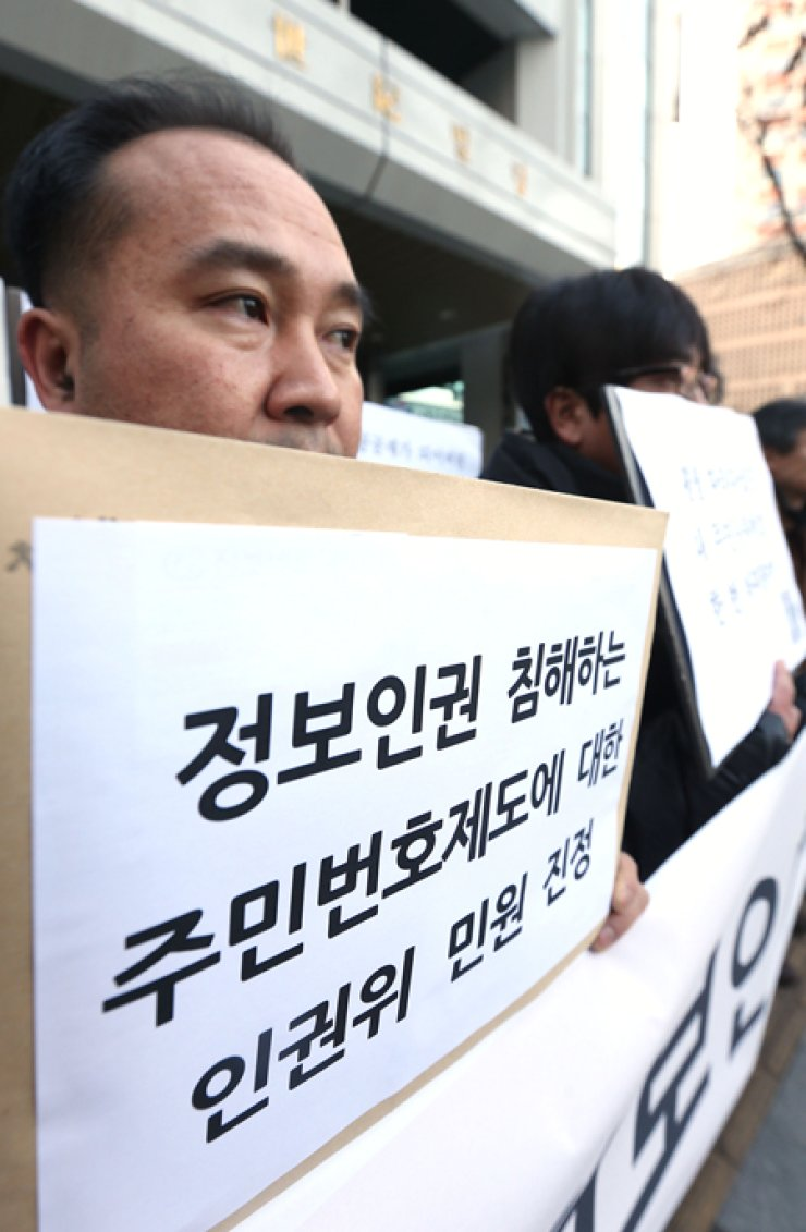 Activists demand an overhaul of the country's identification system based on 'resident registration numbers' during a rally in front of the National Human Rights Commission in Seoul, Wednesday. / Yonhap