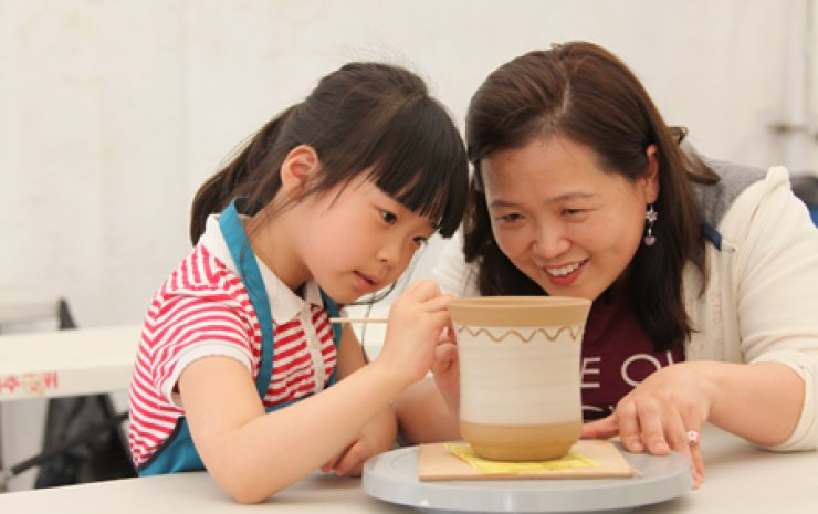 A child paints on a vase that underwent firing during last year's Icheon Ceramic Festival in Icheon, Gyeonggi Province./ Courtesy of Icheon Ceramic Festival organizer
