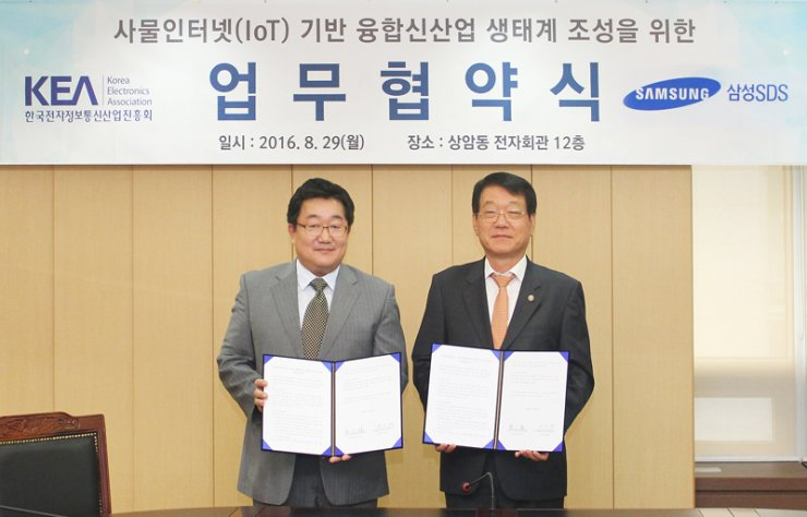 Samsung SDS Industrial IoT Business Group head Chae Gyoung-il, left, poses with Korea Electronics Association (KEA) Vice Chairman Nam In-seok after signing an agreement to cooperate on supporting the Internet of Things (IoT) business of small enterprises at the KEA office in Sangam-dong, western Seoul, Monday. / Courtesy of Samsung SDS