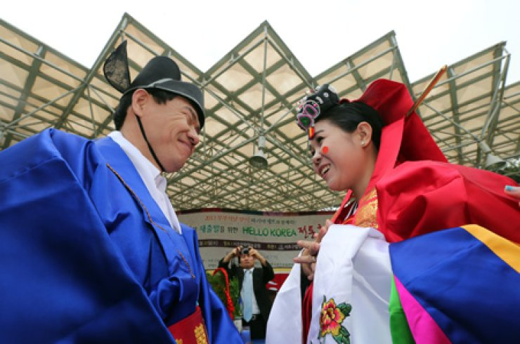 A Korean groom and a foreign bride smile at each other during their traditional Korean wedding ceremony with other four couples in a park in Yangjae-dong, southern Seoul, May 22. The Ministry of Justice announced a plan to tighten rules on issuing marriage visas at the end of last month, drawing a mixed reaction from migrant women. / Yonhap