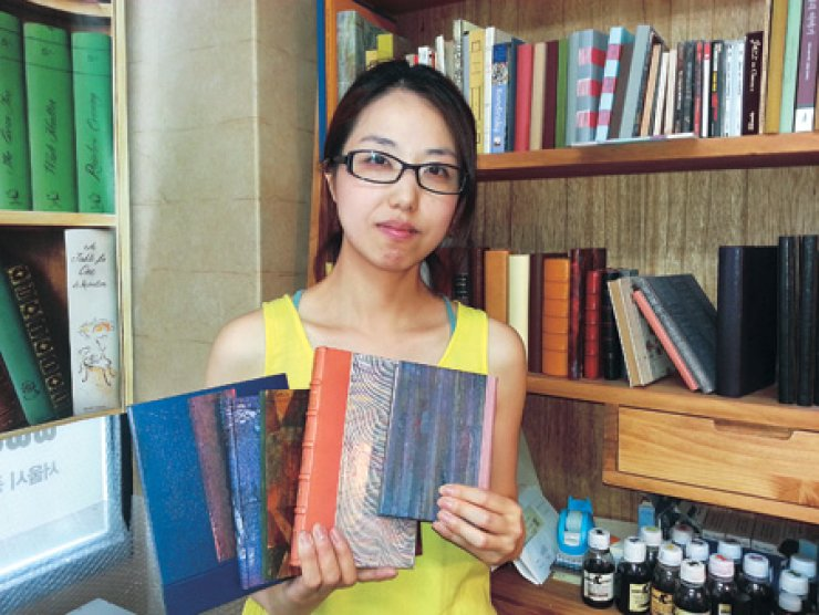 Bookbinding artist Lee Bo-young poses with samples of her work in her studio in Seoul, June 27. / Korea Times photo by Kim Se-jeong