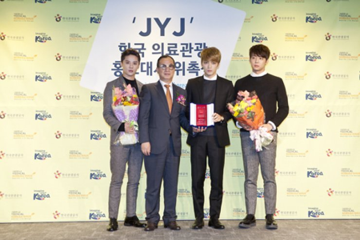 Korea Tourism Organization CEO Byun Choo-suk, second from left, poses with boy band JYJ at the organization's building in Seoul after appointing them as publicity ambassadors for Visit Medical Korea, a website on the nation's medical tourism industry, Wednesday./ Courtesy of Korea Tourism Organization