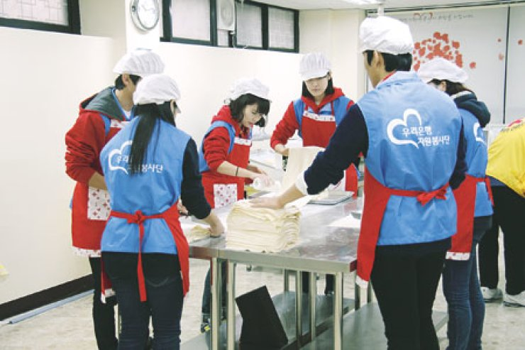 New employees at Woori Bank make bread and noodles at a branch of the Red Cross in Seoul earlier this month. / Courtesy of Woori