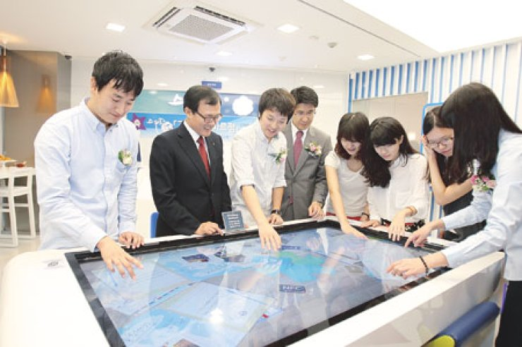 Woori Bank CEO Lee Soon-woo, second from left, uses a 'media table' with students of Korea University at the lender's first smart branch in the neighborhood of the college in northern Seoul, September.  / Courtesy of Woori