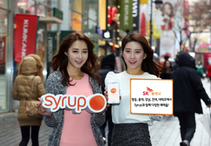 Models promote SK Planet's Syrup, a mileage app powered by Bluetooth Low Energy (BLE), during a promotional event in Myeong-dong, Seoul, Tuesday. SK Planet said the Syrup service will provide users with extra benefits that will be available at stores in five major business districts such as Hong-dae,Gangnam, Myeong-dong and Daehak-ro. / Courtesy of SK Planet