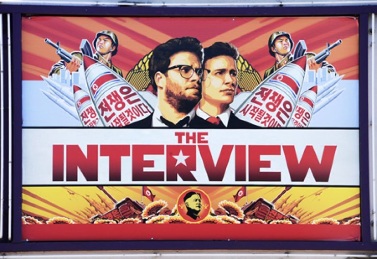 A poster for 'The Interview,' a farcical comedy about a plot to assassinate North Korean leader Kim Jong-un, is displayed on the marquee of a theater in Los Angeles, on Dec. 25. / AFP-Yonhap